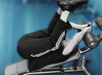 Jak ćwiczyć mięśnie brzucha - unoszenie nóg w leżeniu na ławce skośnej